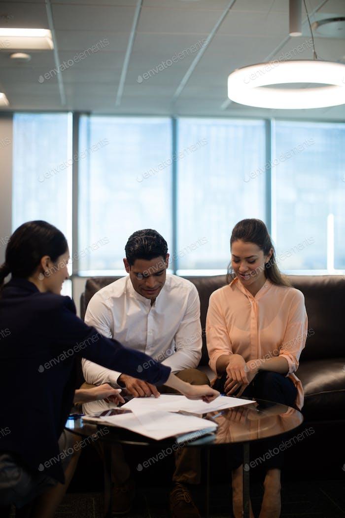 Businesswoman explaining plans to colleagues