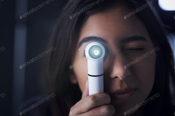 Female doctor using otoscope for examination