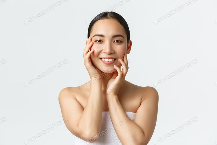 Gorgeous sensual asian woman in towel touching face and smiling, applying skincare products