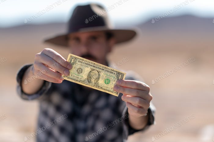Cowboy with grey hat, moustache and checked shirt holding a dollar bill