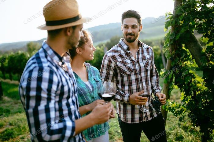 Happy young people tasting wine in vineyard