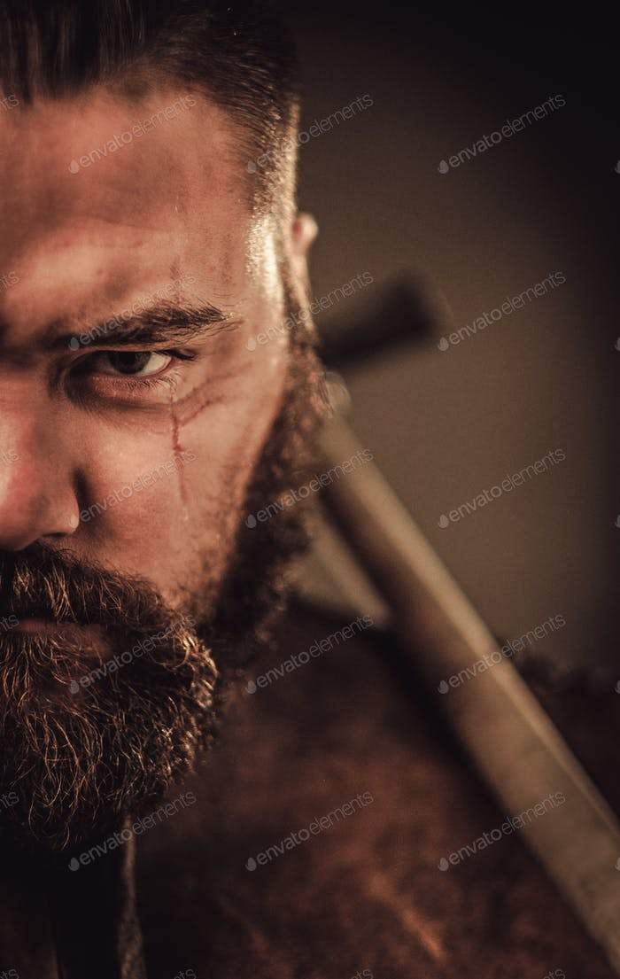 Angry viking with ax in a traditional warrior clothes, posing on a dark background.