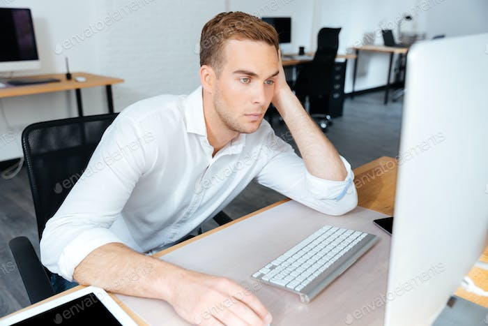 Tired bored young businessman working with computer in office