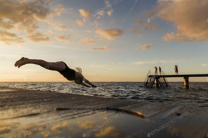 Frau Tauchen in das Meer bei Sonnenuntergang