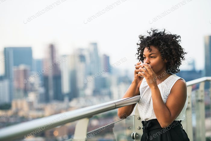 A portrait of a woman standing on a terrace, drinking coffee.