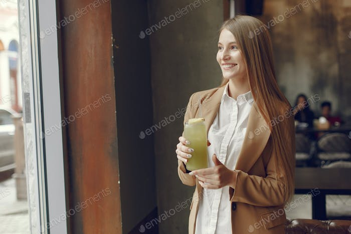 Elegante Frau steht in einem Café und trinkt einen Cocktail