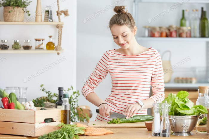 Woman cutting a cucumber
