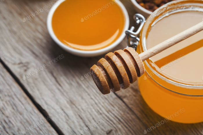 Closeup of liquid honey on wooden background