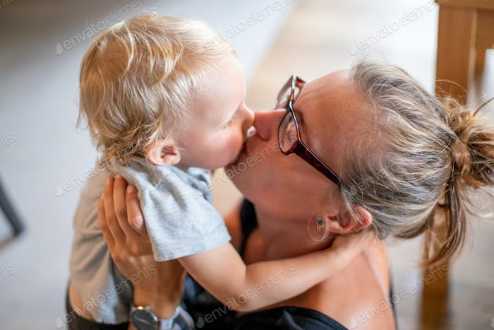 Young mom kissing his child son at home