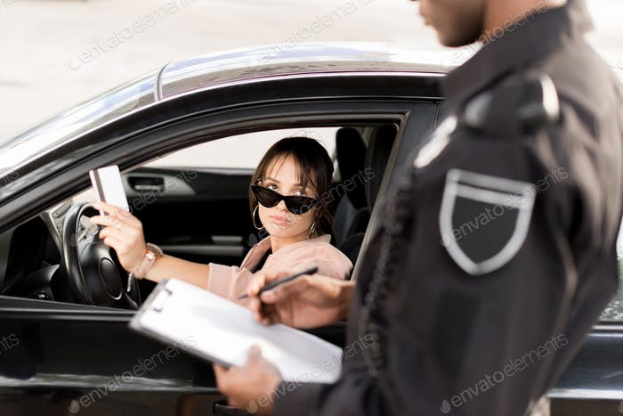 Cropped image of policeman with clipboard and pen talking to young driver in car giving driver