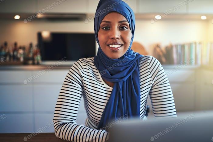 Smiling Arabic female entrepreneur using a laptop in her kitchen