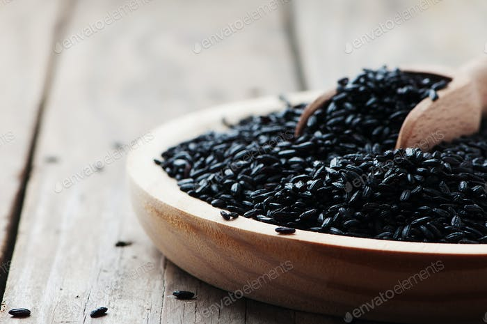 Black uncooked rice on the wooden table