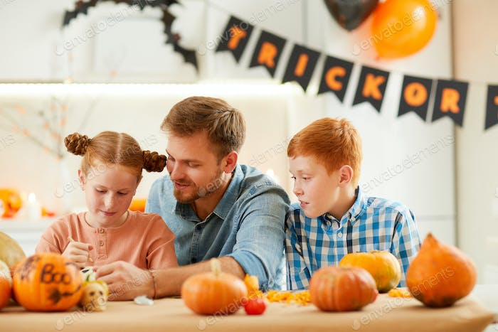 Family decorating pumpkins for holiday