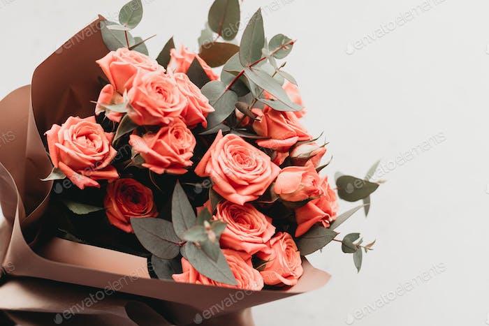 Bouquet wird aus Korallensprührosen und Eukalyptuszweigen hergestellt.