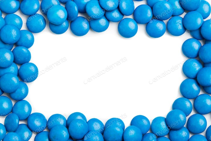 Frame of blue chocolate candy on white background with space