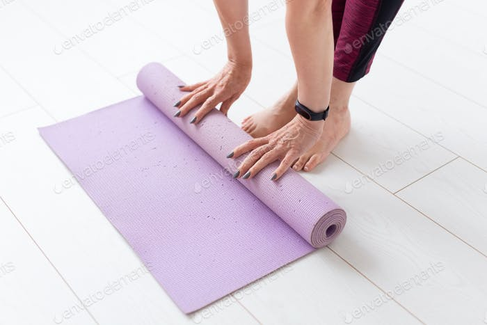 People, sport and healthcare concept - Middle-aged woman with grey nails rolling her mat after a