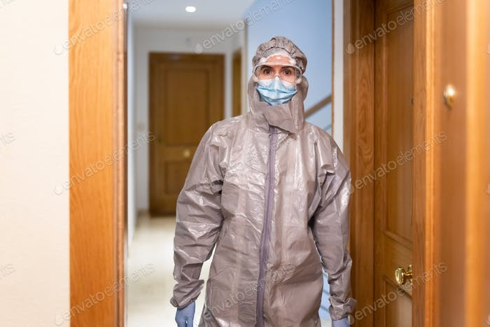 Doctor in PPE Personal Protective Equipment coming into the house