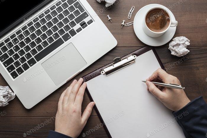 Geschäftsfrau am Bürotisch mit notepad und computer