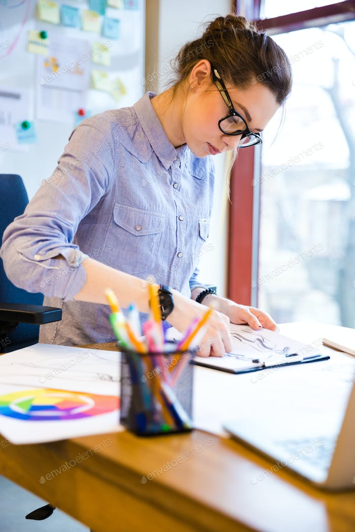 Focused woman fashion designer drawing sketches on workplace