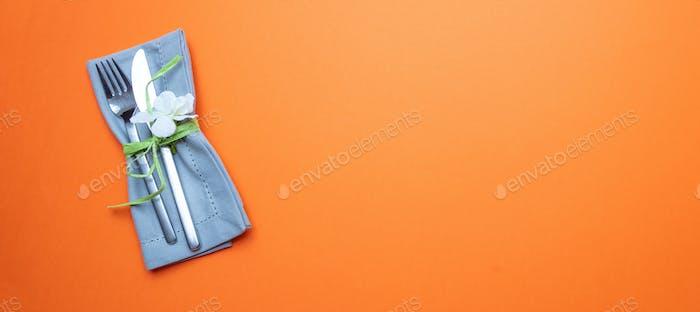 Tischplatzierung in orange. Graue Leinenserviette und Besteck auf orangefarbenem Hintergrund