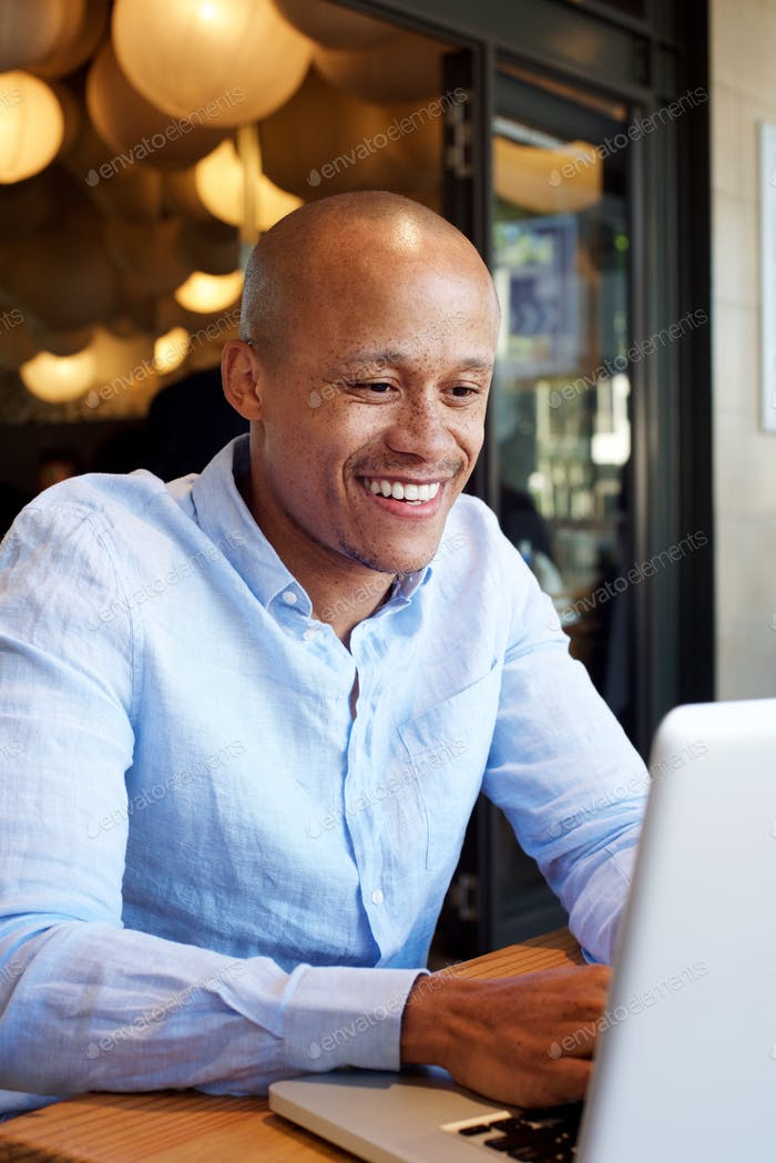 smiling african businessman working on laptop