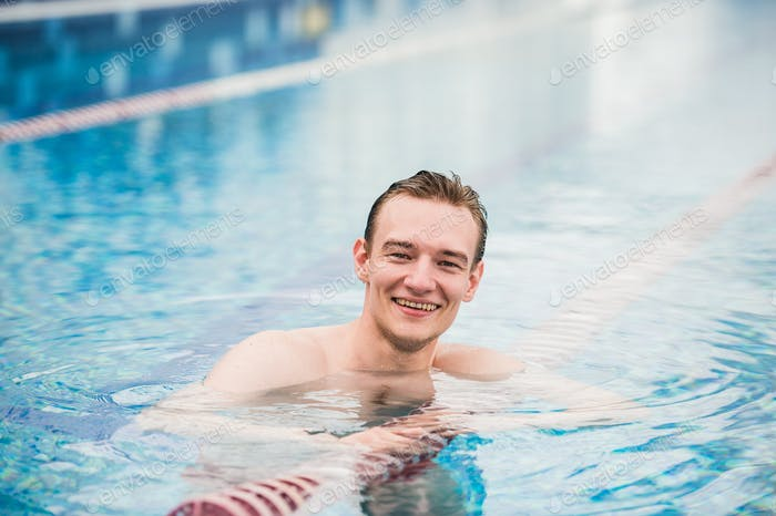Handsome athletic male posing in a swinning pool