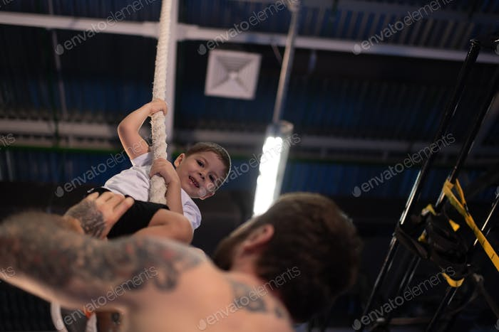 Father teaching happy boy to climb rope in gym
