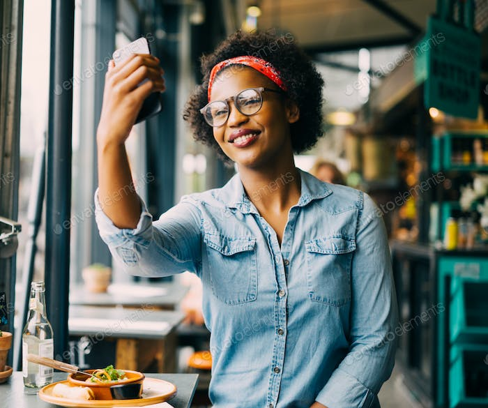 Smiling young woman taking selfies over lunch in a bistro