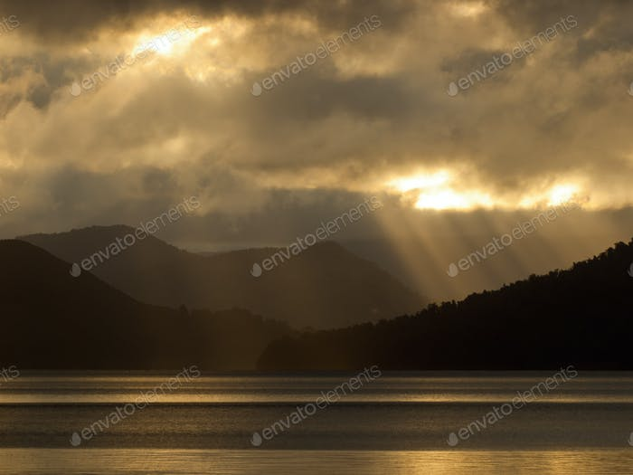sun through clouds over lake