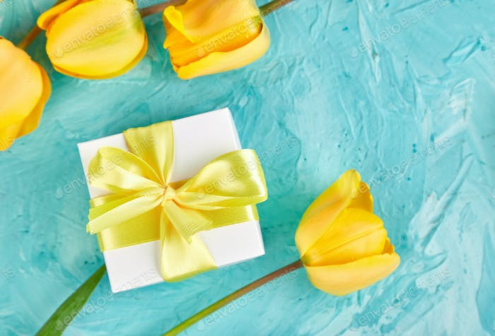 Gift box with yellow ribbon near tulip