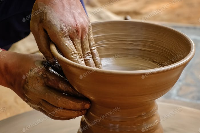 Pottery - skilled wet hands of potter shaping the clay on potter wheel