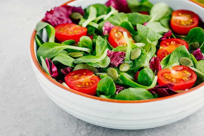 Fresh green salad bowl with radicchio, tomatoes and pumpkin seeds.