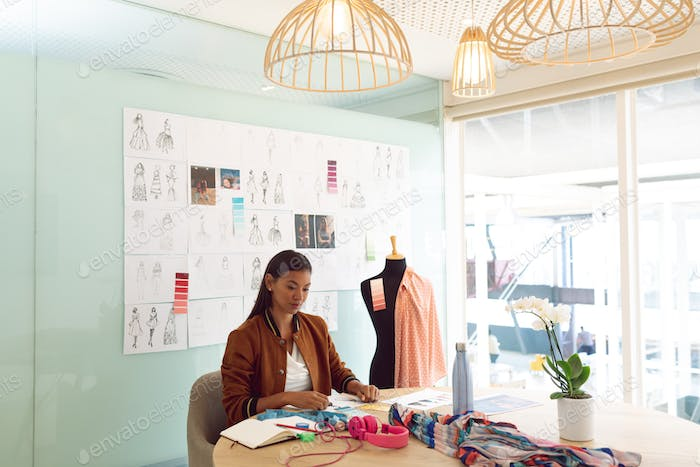 Side view of beautiful mixed race female fashion designer working at table in a modern office