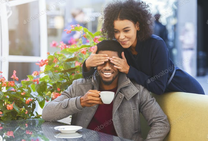 Black woman standing behind her man and closing his eyes