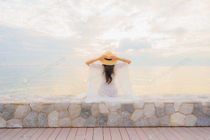 Retrato hermoso jóvenes mujeres asiáticas feliz sonrisa relajarse alrededor del mar playa océano
