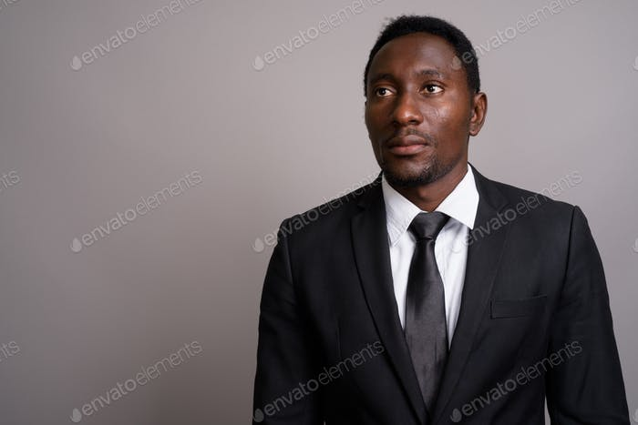 Thumbnail for Young handsome African businessman against gray background