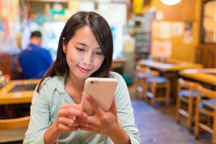 Frau mit Blick auf Handy im japanischen Restaurant