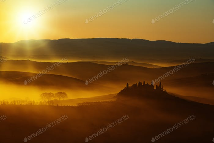 sunset light on rolling hills in Tuscany