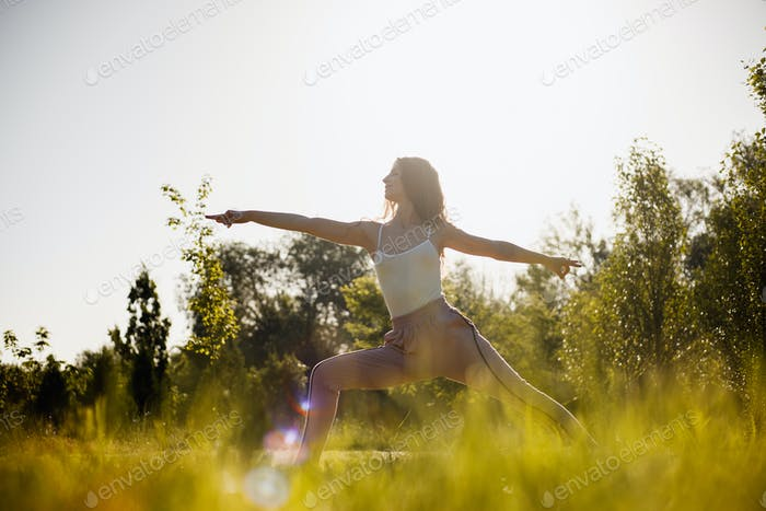 Young woman in yoga clothes is practising yoga in the open air in the nature on the grass on the