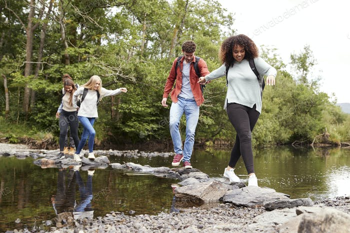 Five mixed race young adult friends hold hands and help each other while crossing a stream