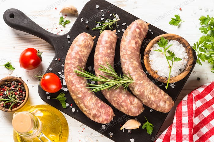Bratwurst or sausages on cutting board at white wooden table table