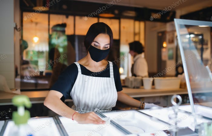 Young woman with face mask working indoors in cafe, disinfecting surfaces