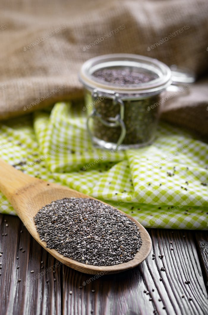 Raw Chia seeds in glass airtight jar and bamboo spatula on woode