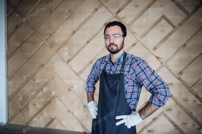Junge männliche Tischler tragen Handschuhe und Brille mit Händen auf Hüften
