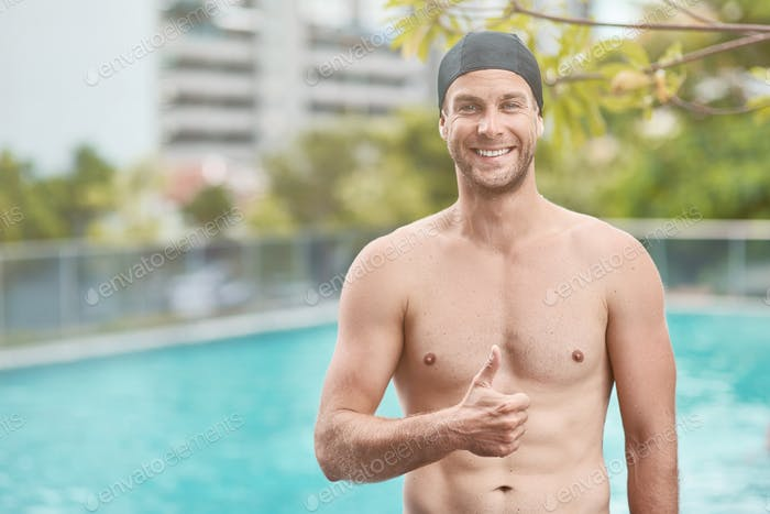 Cheerful swimming instructor thumbing up