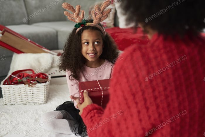 Rear view of mommy giving her daughter the Christmas present