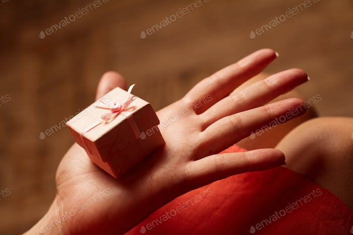 Open hand of a woman holding a small pink gift box