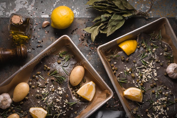 Baking dish with raw flounders and seasoning