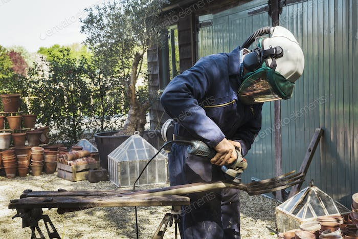 Man standing outdoors, wearing a face mask, working on a metal pitchfork with an angle grinder.