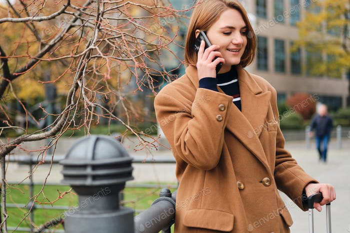 Pretty casual girl happily talking on cellphone standing on city street